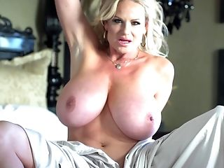 Kelly Madison enjoys a solo session on her big bed