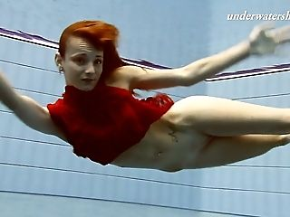 Redhead beauty Ala swims under the water in the pool